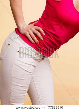 Detailed fashion and clothes concept. Closeup photo of woman outfit colorful details. Red tank top and white trousers