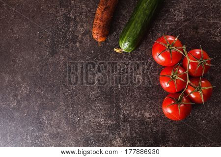Red tomatoes carrot green cucumber lying on a dark marble table. Space for text and design with vegetables. Flat lay vegetables, copyspace.