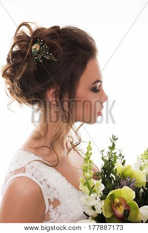 Young attractive bride with the bouquet of flowers. Jewelry on the head.