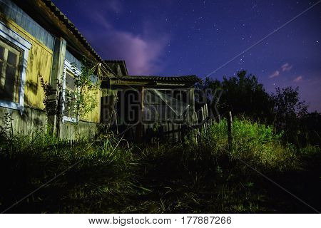 Old ramshackle house. The beautiful night scenery. Slow shutter speed. Spectacular clear starry sky in night. Scenic view. Green grass