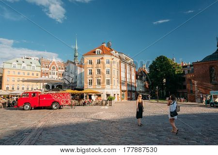 Riga, Latvia - July 1, 2016: Two Young People Women Walking And Taking Pictures In Street Dome Square In Sunny Summer Day With Blue Sky