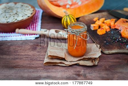 Pumpkin juice in a glass jar on a table in the middle of spices and sliced pumpkin