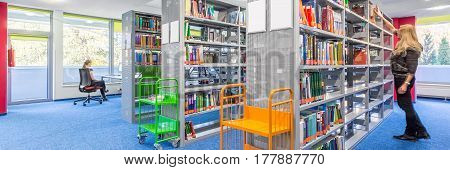 Panoramic view of light library interior with modern shelves and colorful trolley