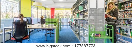 Panorama of colorful library interior with computer workstation and modern shelving