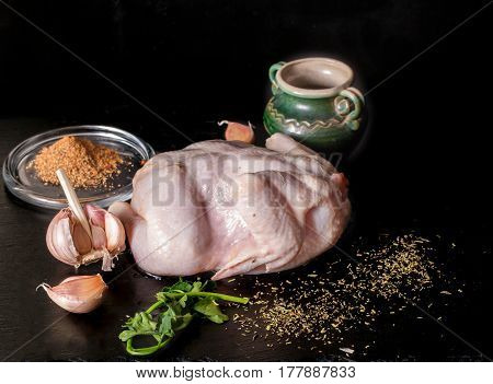 Carcass of raw chicken and spice against a dark background. On a board from slate chicken garlic segments greens and sauce lie