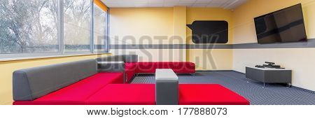 Panorama of modern university tv room for students to relax with extra large sofa
