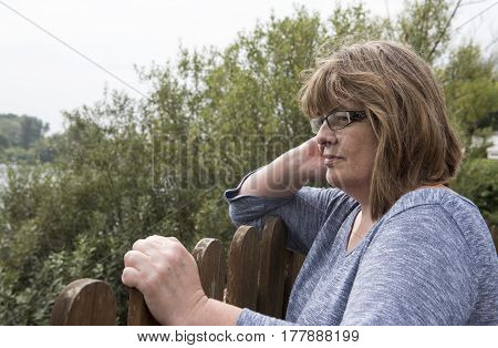 Portrait image of a mature woman resting on a fence, looking out at a view. Fed up facial expression.