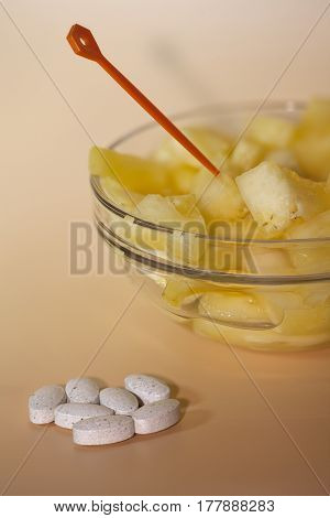 handful of pills and cup filled with pineapple slices concept of healthy nutrition and prevention medicine