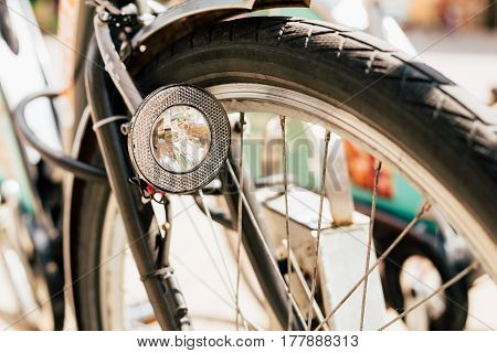 Close Up Of Bike Headlight And Wheel Of Bicycle On Street. Bike Lamp In Bokeh Background.