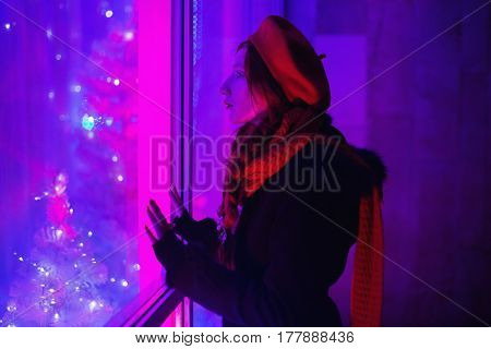 A woman in night street with red curly hair braided in a braid in a black coat a scarf around his neck and a red beret looking out the window with a blue light. Red-haired girl with bright unusual appearance in street.