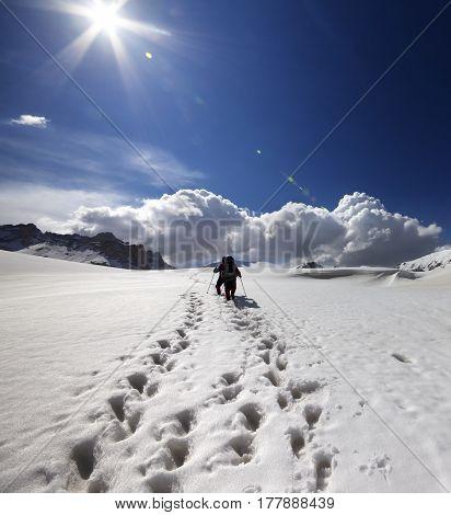 Two hikers on snow plateau at sun day. Turkey Central Taurus Mountains Aladaglar (Anti-Taurus) plateau Edigel (Yedi Goller)