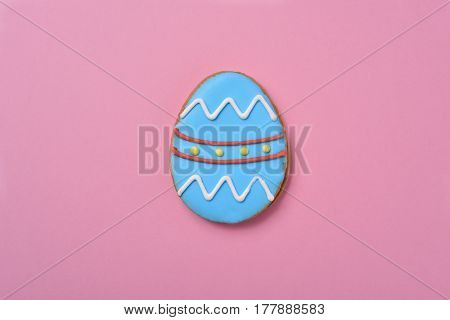 closeup of a cookie decorated as a blue easter egg against a pink background, with some blank space around it