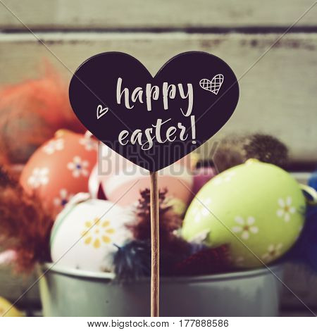 a heart-shaped black chalkboard with the text happy easter written in it and pile of different decorated easter eggs and feathers of different colors in a bucket in the background