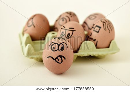 a pile of brown eggs ornamented with funny faces in a yellow egg carton, on an off-white background