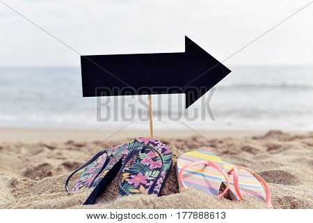 closeup of a blank black signboard in the shape of an arrow sign and two pairs of flip-flops on the sand of a beach