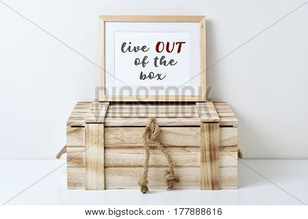 a wooden-framed picture with the text live out of the box written in it placed on a rustic wooden box, against an off-white background