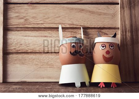 a pair of easter eggs decorated with funny faces, placed on a rustic wooden surface, against a rustic wooden background