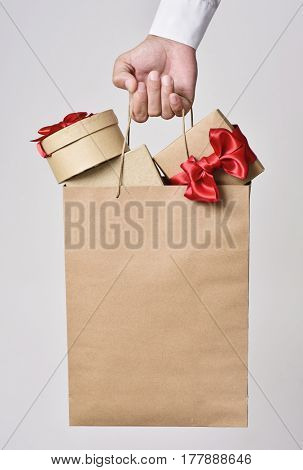closeup of the hand of a young caucasian man carrying a paper shopping bag full of gift boxes ornamented with red ribbon against an off-white background, with a blank space in the bag