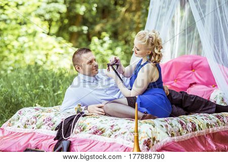 Man and woman sitting on the bed in the lawn and woman undressing man in Lviv, Ukraine.
