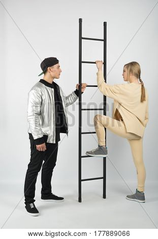 Modern fashionable hipster couple with ladder. Young muscular man wearing black clothes and sneakers with girl in yellow clothes on white background. She is climbing on the step of ladder