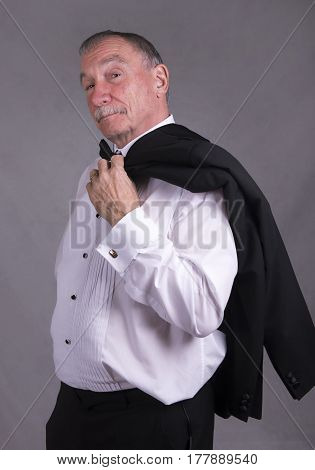 Portrait image of a mature man in a suit fixing his bow tie, holding a dinner jacket. Taken on a grey background. Vertical image.