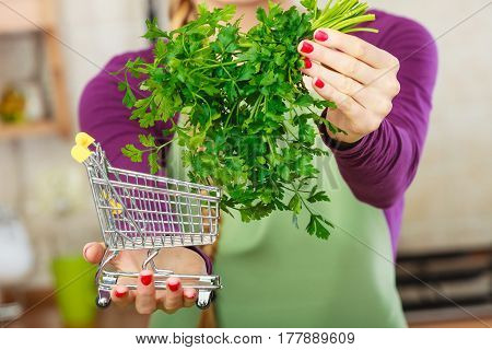 Woman Holding Shopping Cart With Parsley Inside