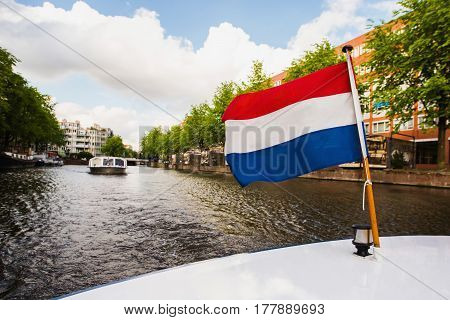 Dutch flag. Spring sunny Amsterdam. The bright clear blue sky with white clouds. Boat trip on the canals of Amsterdam with flag. The bridge over the water. Travel to Europe