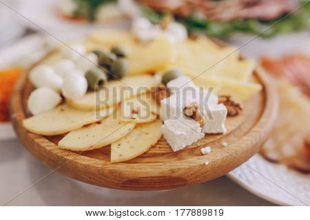 Different kinds of cheese on a wooden plate