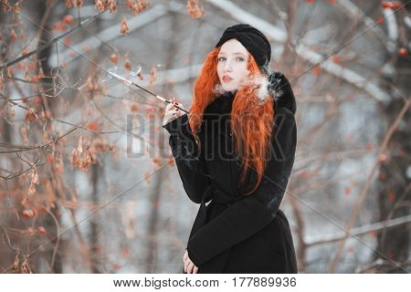 Elegance woman with red hair in a black coat on background of a winter forest with a mouthpiece in hand. Red-haired  elegance girl with bright appearance with a turban on her head with a cigarette. Smoking aesthetics