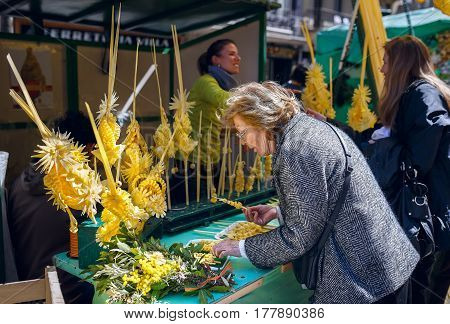 BARCELONA/ SPAIN - MARCH 28, 2015. An elderly lady buying a traditional decoration made of palm branches for Palm Sunday celebration at the Easter market. Barcelona, Spain