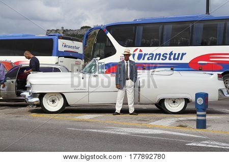 Havana, Cuba, January 1, 2000 - Chauffeur driver standing beside a limousine waiting for people from tourist bus