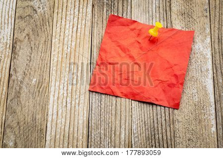 blank red crumpled sticky note against grunge painted wood - ready for a reminder message