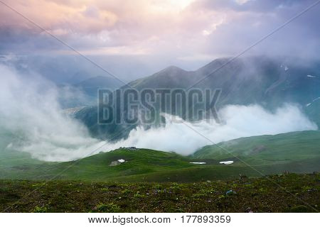 Form a green lawn opens a beautiful fascinating view fog high mountains and rays of sun. Upper Svaneti Georgia Europe.