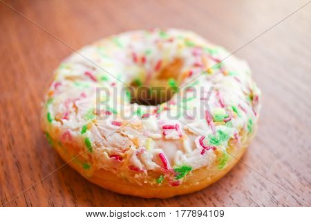 Donut With White Icing And Sprinkles On Wooden Background Table