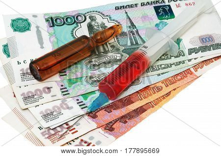 Syringe with the needle with medicine ampule and rubles on white background