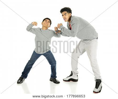 A elementary boy ready to take a punch at his tall big brother.  On a white background.