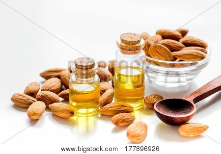 natural cosmetic set with almond oil and bowl of almonds on light table background