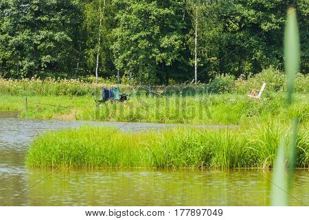 Beautiful view of lake, fishing rods, green forest , blue sky. Fishing in lake, concept of a rural getaway and fishing. For modern nature background, backdrop, substrate, composition use