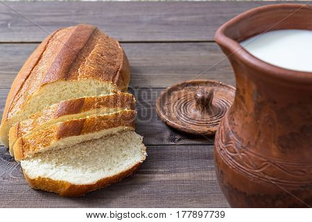 Milk and bread. Milk in a  clay jug. Wheat bread on a wooden background. Bio products.  Healthy food