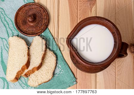 Milk and bread. Milk in a  clay jug. Wheat bread on a wooden background. Bio products.  Healthy food.
