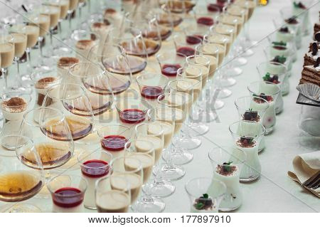 Beautiful row line of different colored alcohol cocktails on a party. Whisky cognac, liquor. Different shapes