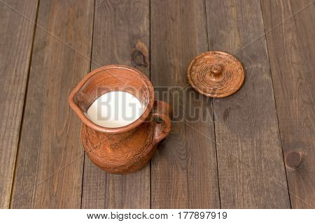 Milk in a  clay jug on a wooden background. Bio products.  Healthy food
