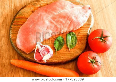 Raw Chicken Fillet Meat With Fresh Vegetables (green Basil Leaves, Red Tomatoes, Garlic, Orange Carr