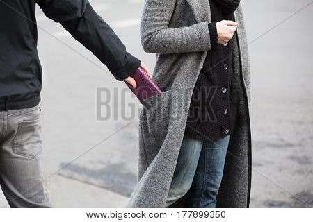 Close Of A Man Stealing Wallet From Woman's Coat Pocket