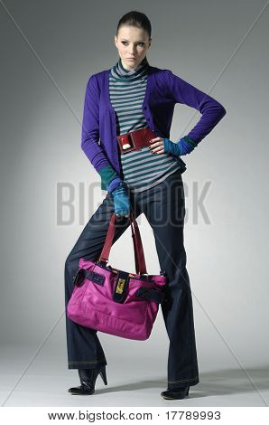 fashion model in autumn/winter clothes holding handbag posing in light background
