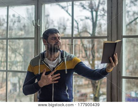 Bearded poet man reads a book with an expression. Big window on background.
