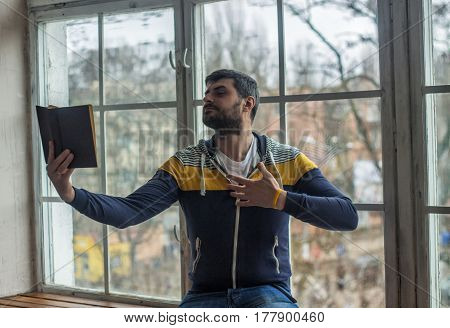 Bearded poet man reads a book with an expression gesture . Big window on background.