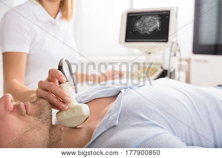 Male Patient Undergoing Ultrasound Of Thyroid Gland In Examination Room