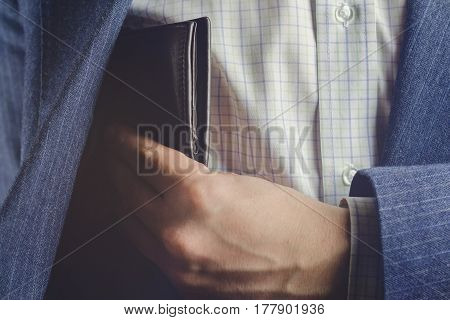 Business man pulls out or put his leather wallet into jacket pocket