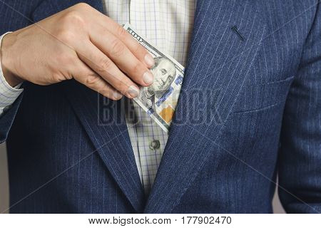 Business man put bundle with hundred dollars into jacket pocket bribery concept